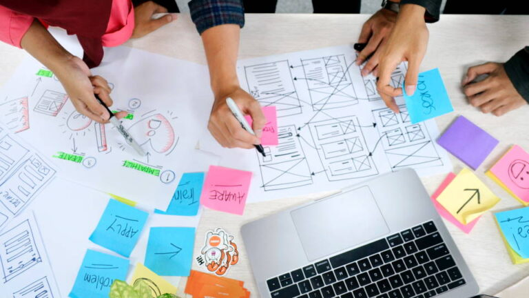 Three people designing a website layout on paper with markers and a laptop